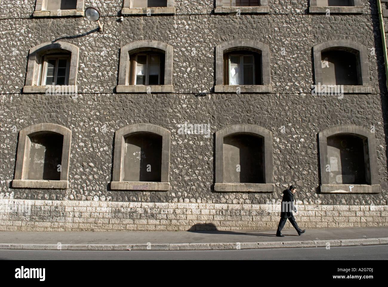 323 eine junge französische männliche Spaziergänge vor der Fassade eines alten Lagers Stockbild