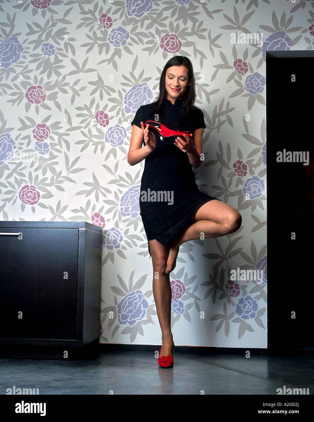 1216452 innen flach Zimmer junge Frau 25 30 Brünette lange Haare rote Schuh Schuhe halten Blick Stand erhöhen Stockbild