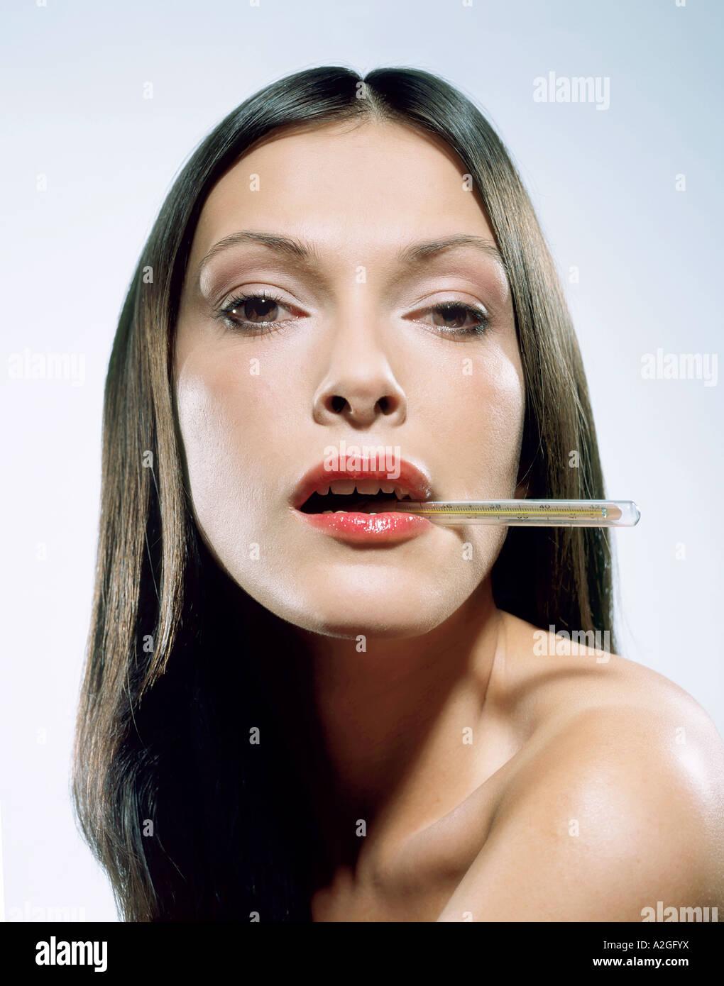 1216635 indoor Studio junge Frau 25 30 brünette Haare lange Thermometer nehmen Temperatur Fieber kalten Mund Stockbild