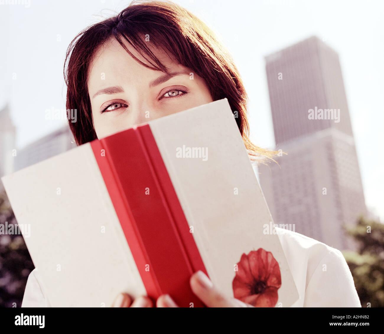 Eine junge 20 s 30 s Frauen tragen weiße Top Standortwahl auf der Wiese in einem Park mit lesen ein Buch Bäume im Hintergrund Stockbild