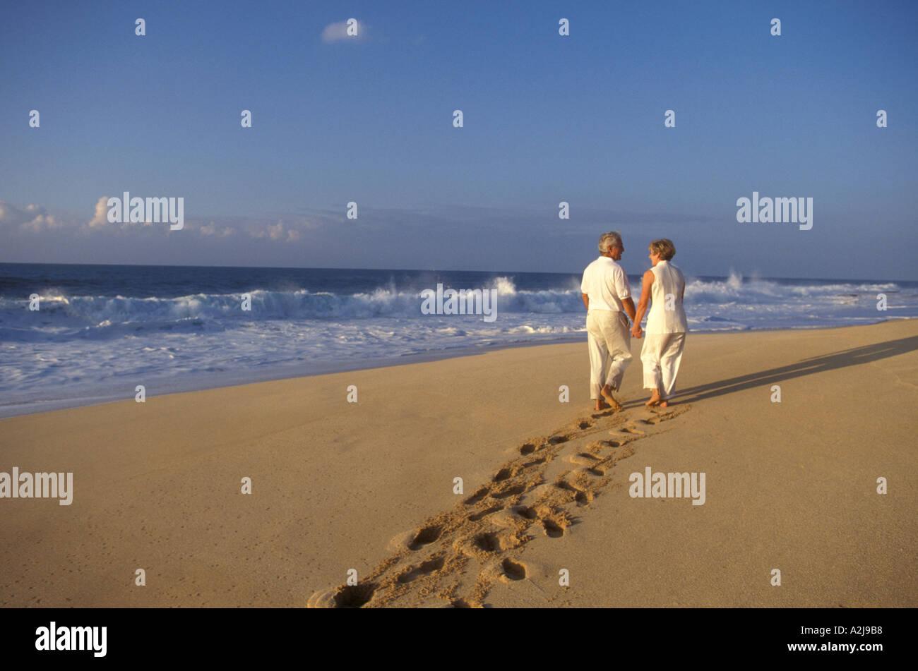 Älteres paar hinterlassen tiefe Spuren im Sand, wie sie zusammen einen leeren Strand zu Fuß und Hand in Hand Stockfoto