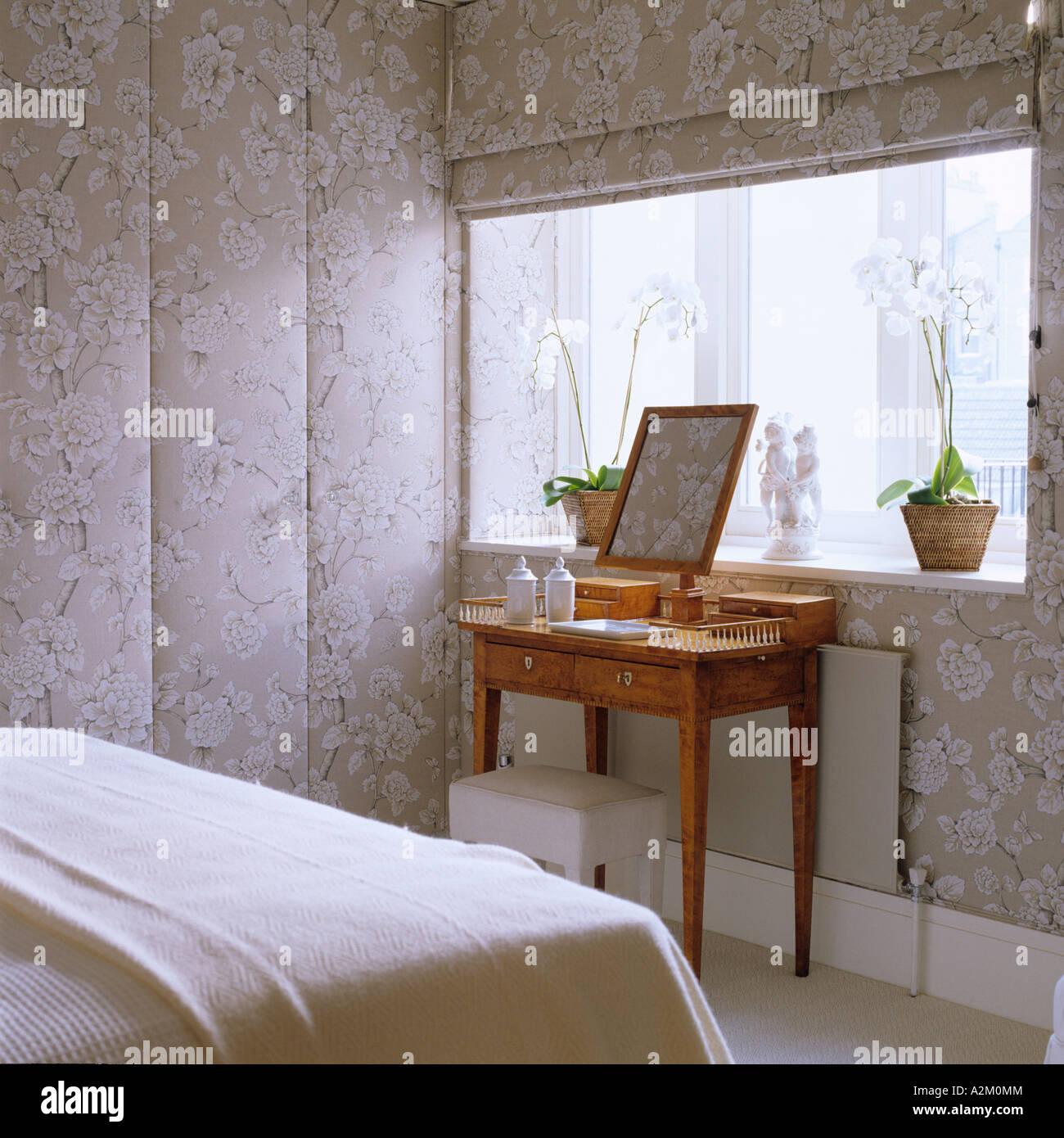 Schminktisch im Schlafzimmer mit floral gemusterten Tapeten und ...