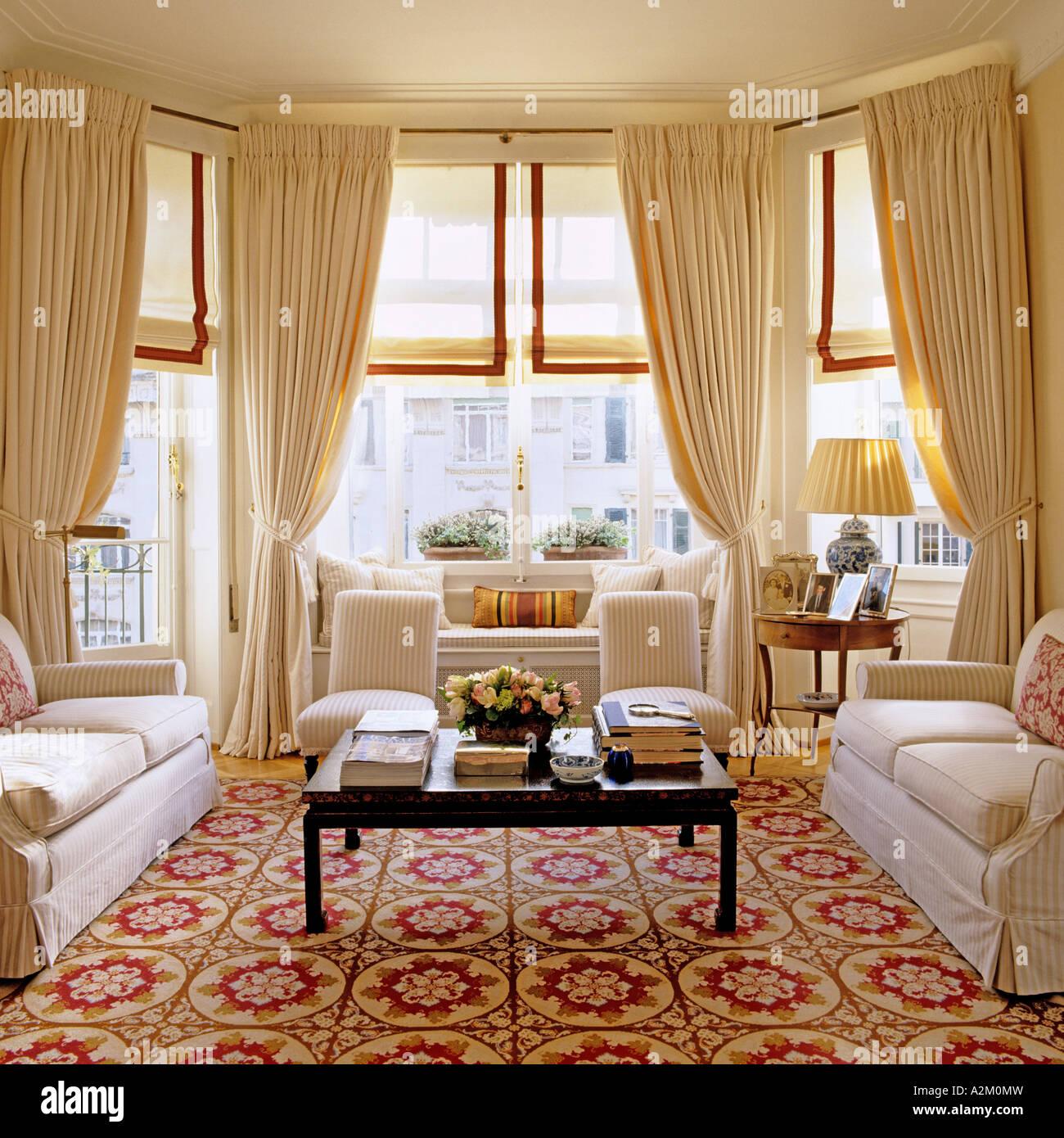 Großes Wohnzimmer mit Erker, drei Sofas und gemusterten Teppich Stockbild