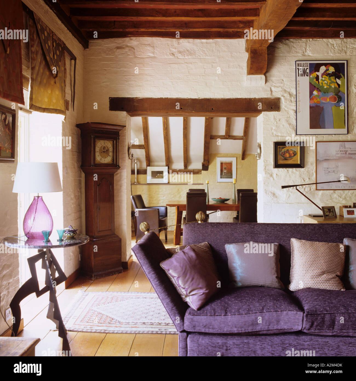 Lila Sofa im Wohnzimmer mit Holzbalken Decke und Katze-Folie Dach ...