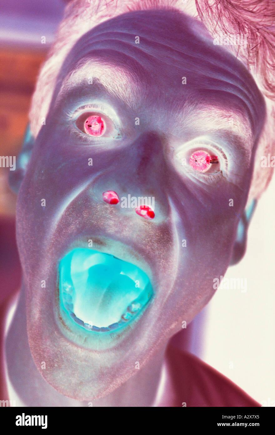 Close-up Portrait des Mannes Gesicht schreien. Surreal. Negatives Image. Stockfoto