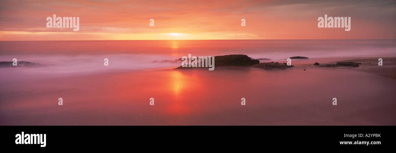 Sonnenuntergang Lichtmalerei Wellen über sandigen Ufer Stockbild