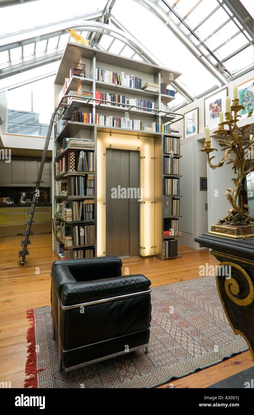 moderne penthouse wohnung, wohnzimmer mit schwarzem leder stuhl, bücherregal und aufzug eingang, Design ideen