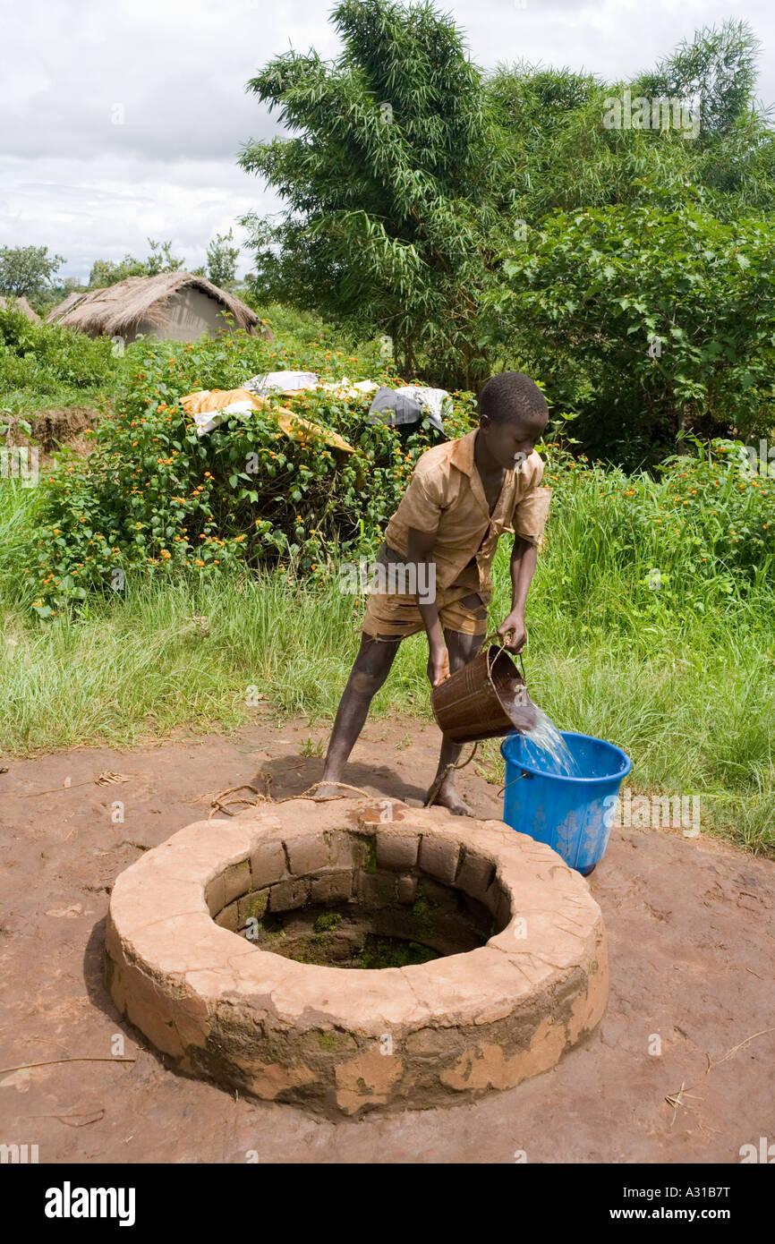jungen ziehen wasser aus einem brunnen in dem dorf von mombala mambala malawi afrika. Black Bedroom Furniture Sets. Home Design Ideas