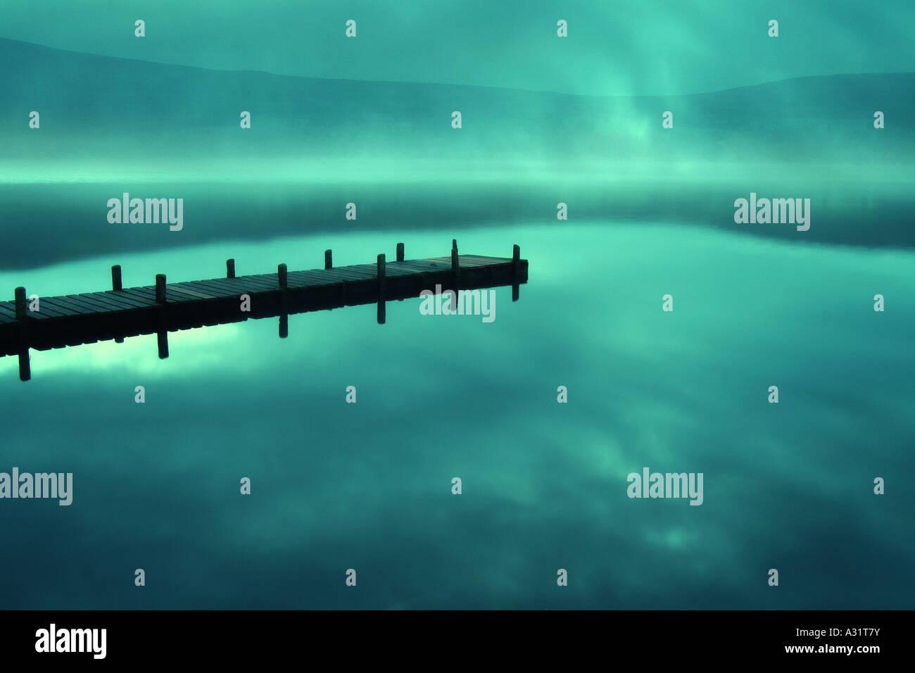 Steg an einem nebligen See Stockbild