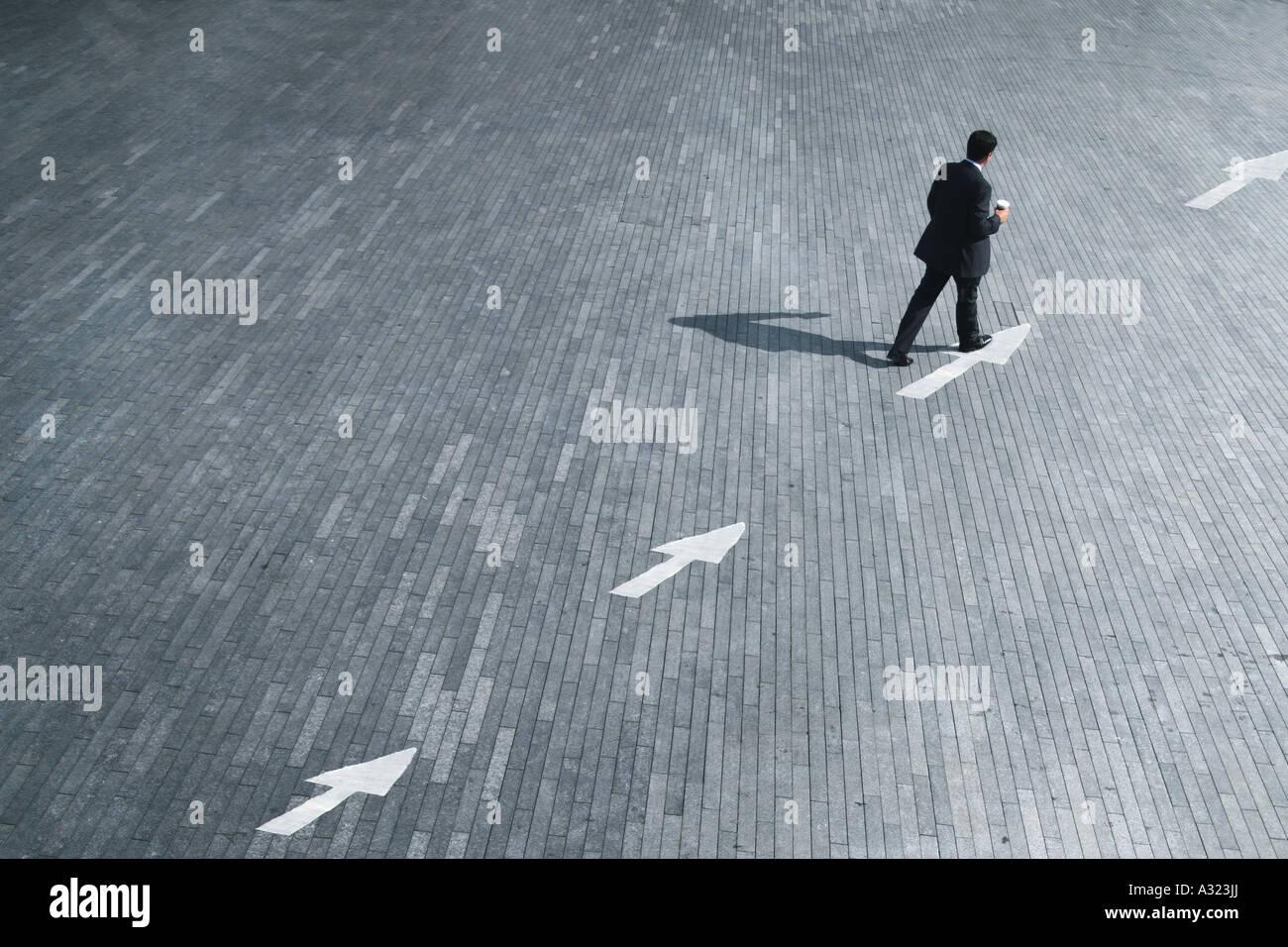 Business-Konzept eines Mannes nach der Richtung der Pfeile Stockfoto