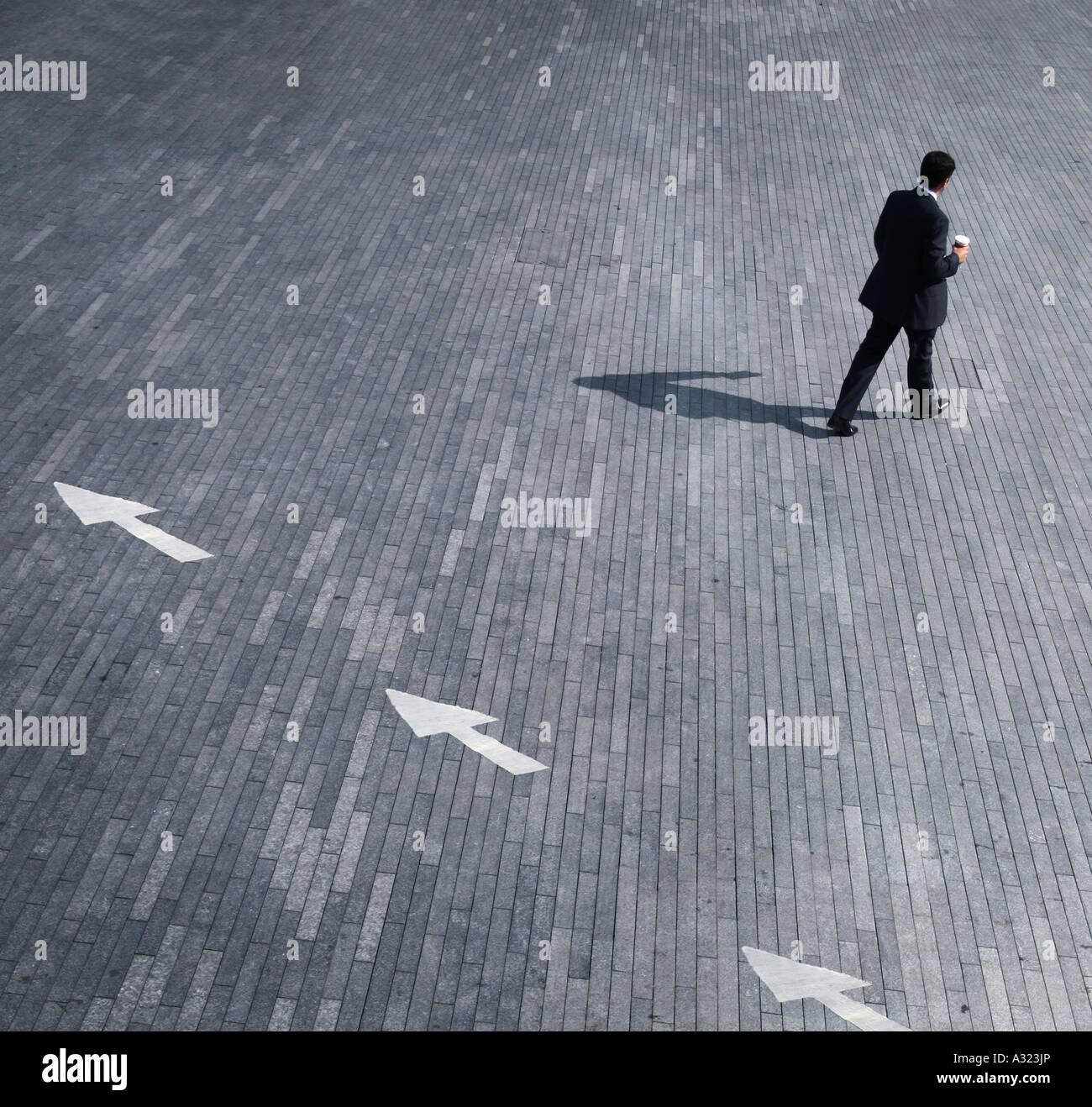 Geschäftskonzept, ein Mann zu Fuß in die entgegengesetzte Richtung der Pfeile Stockbild
