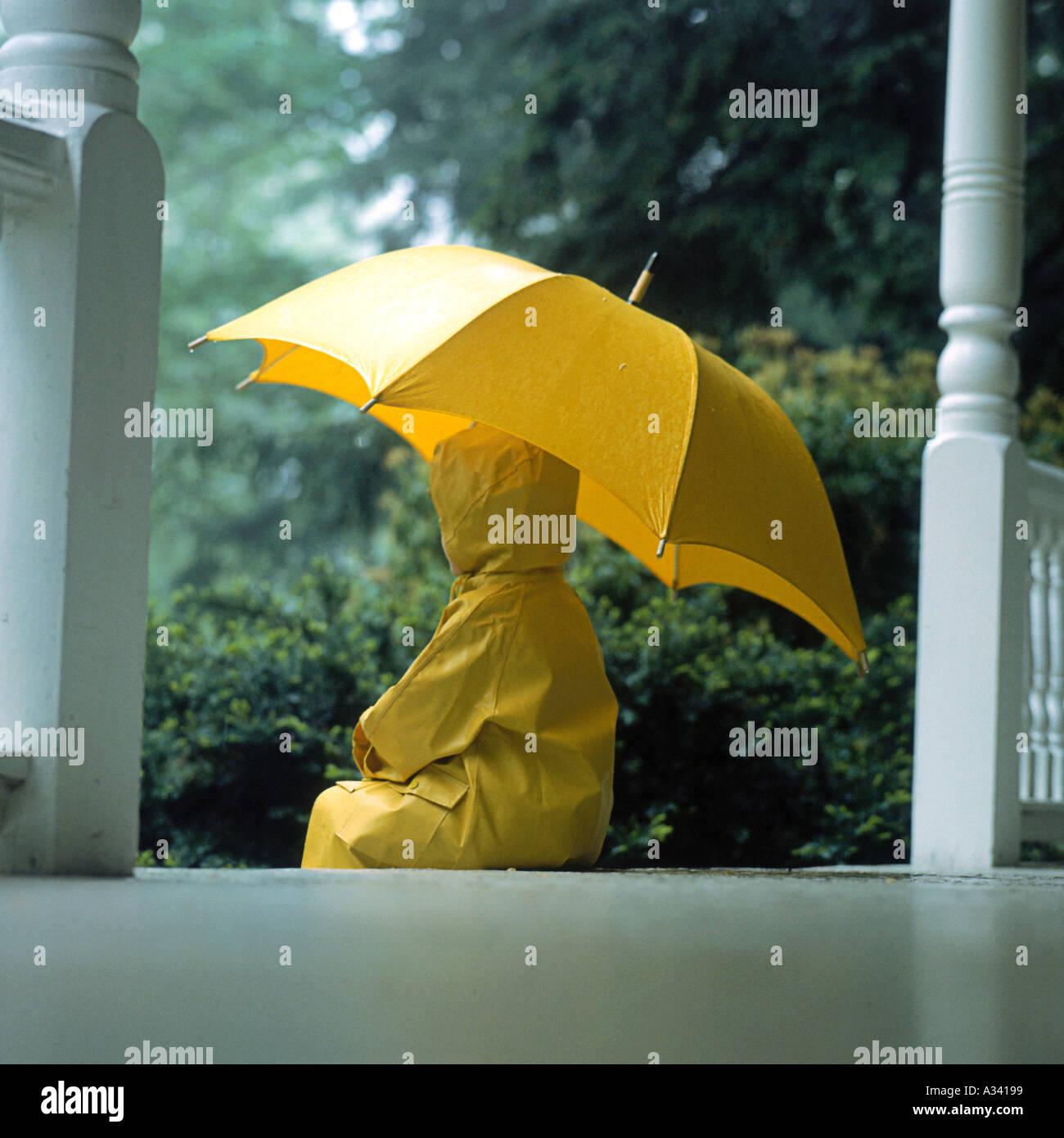 Ein kleines Kind trug einen gelben Regenmantel und Regen Stiefel stehen im Regen halten einen gelben Regenschirm Stockbild