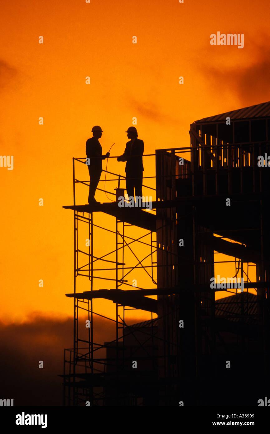 Silhouette von zwei Bauarbeiter auf Hochhaus Contruction Gerüst stehen Stockbild