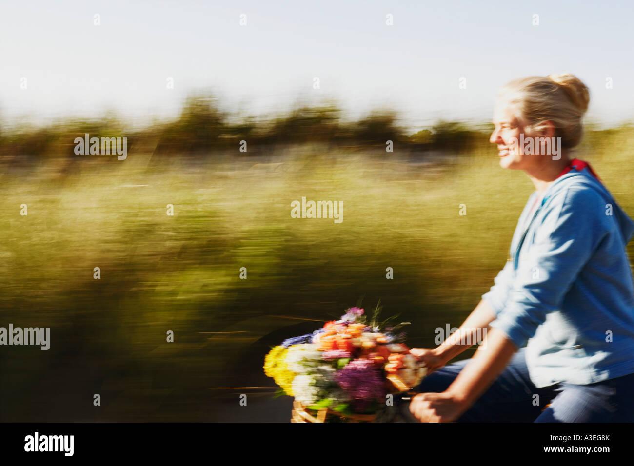Seitenansicht einer reifen Frau, die mit dem Fahrrad Stockbild