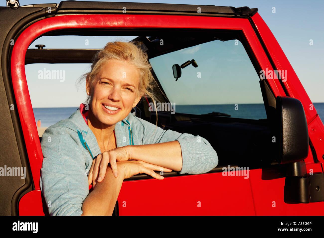 Porträt einer reifen Frau, die an der Fahrzeugtür gelehnt Stockbild