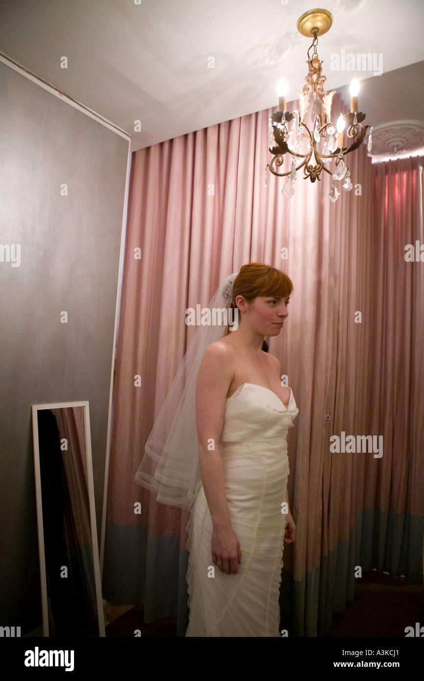 Eine junge Frau schaut sich im Spiegel als sie, auf ein weißes ...