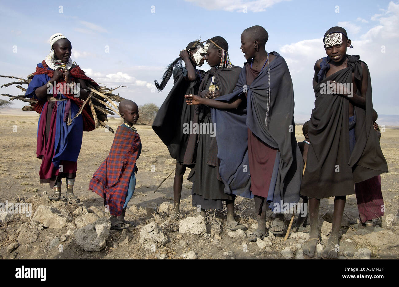 Junge beschnitten vor kurzem Masai Krieger und Masai Mädchen in den Serengei-Ebenen-Tansania Stockbild