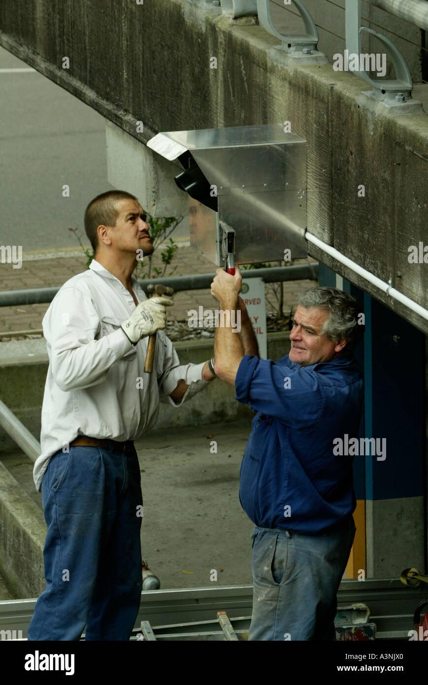 Arbeiter installieren Überwachungskamera Stockfoto