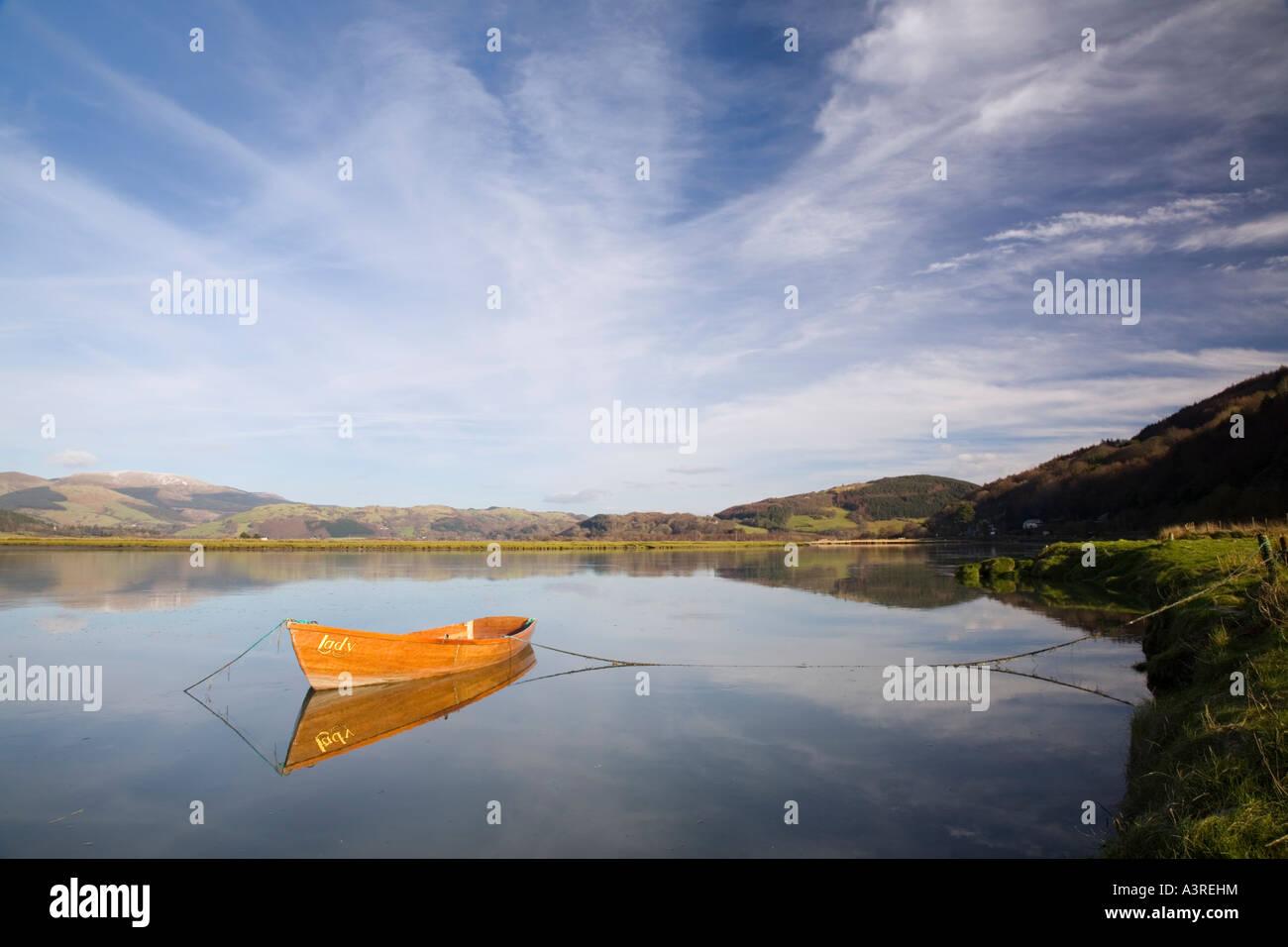 Landschaftlich schöne Aussicht mit hölzernen Ruderboot spiegelt sich in ruhigem Wasser auf River Dovey Stockbild