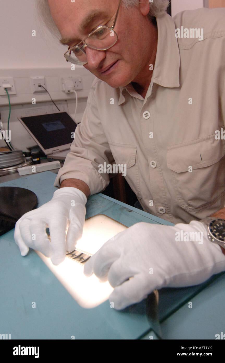 qualifizierten männlichen Restauratorin arbeiten auf die Wiederherstellung und Erhaltung der alten Filmmaterial Stockbild