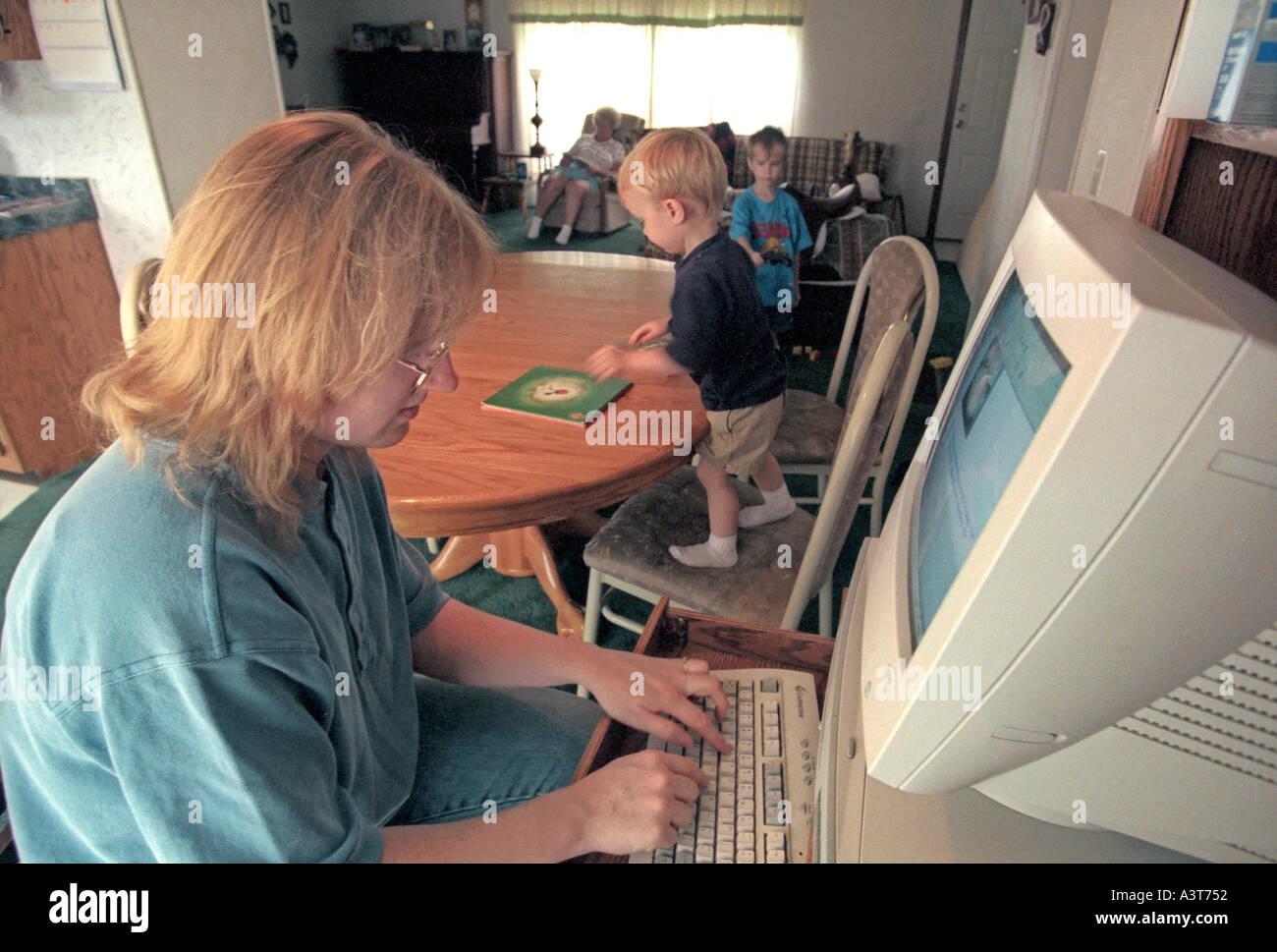 Kind spielt, während Mutter am Computer ihr home based Business arbeitet Stockfoto