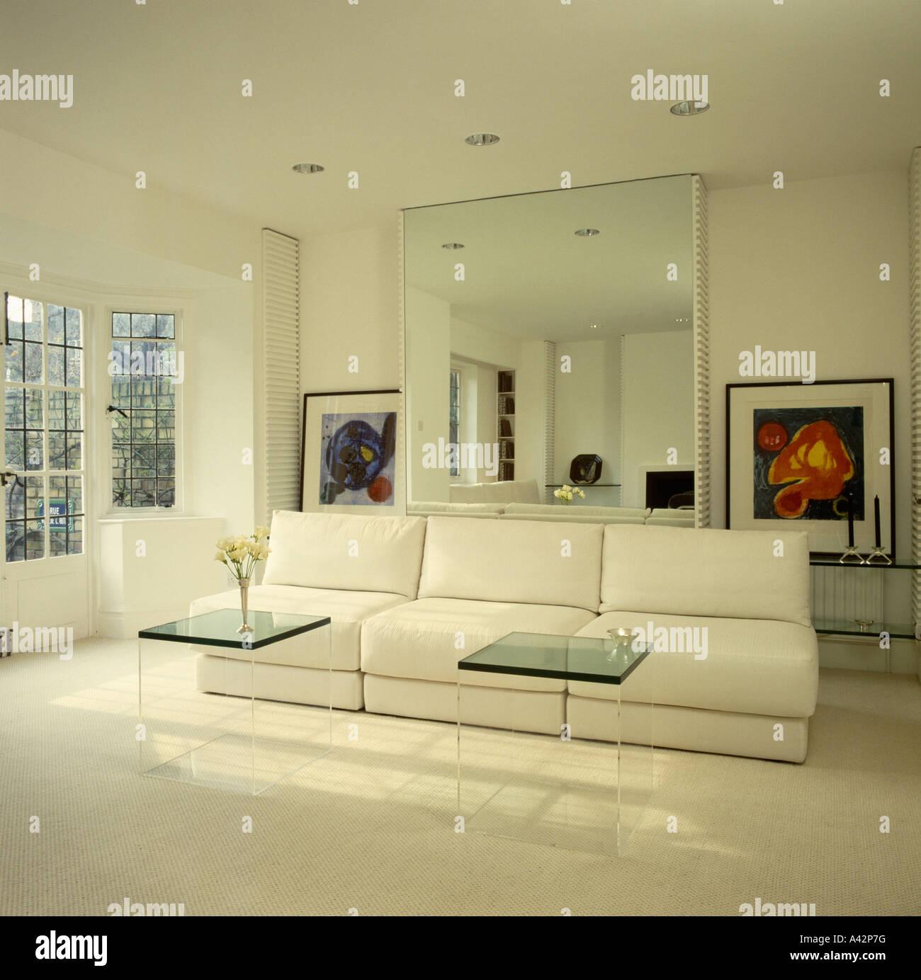 Plexiglas-Couchtische vor großen weißen Sofa im Wohnzimmer moderne