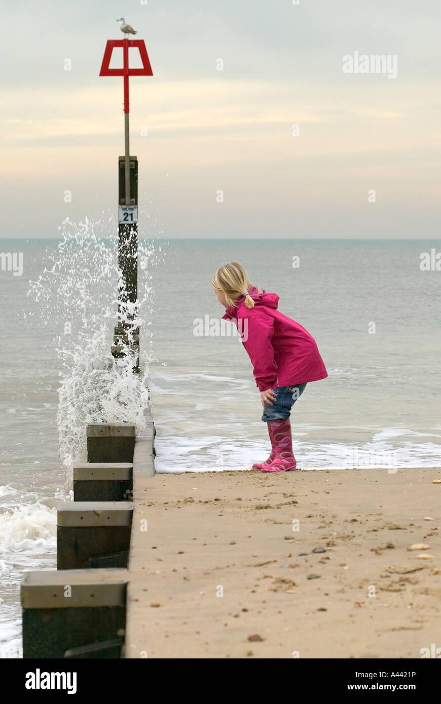 Junge Mädchen beobachten, wie die Wellen gegen die Flut-Wand Stockbild