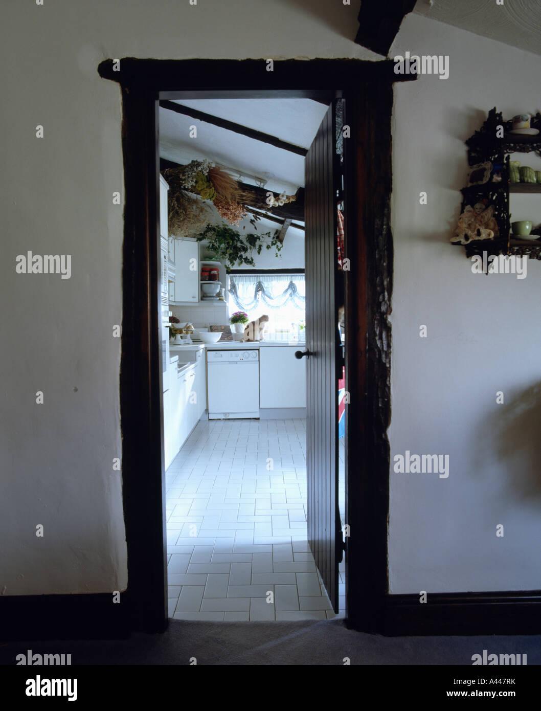 Blick durch die offene Tür für traditionelle weiße Landhaus-Küche ...