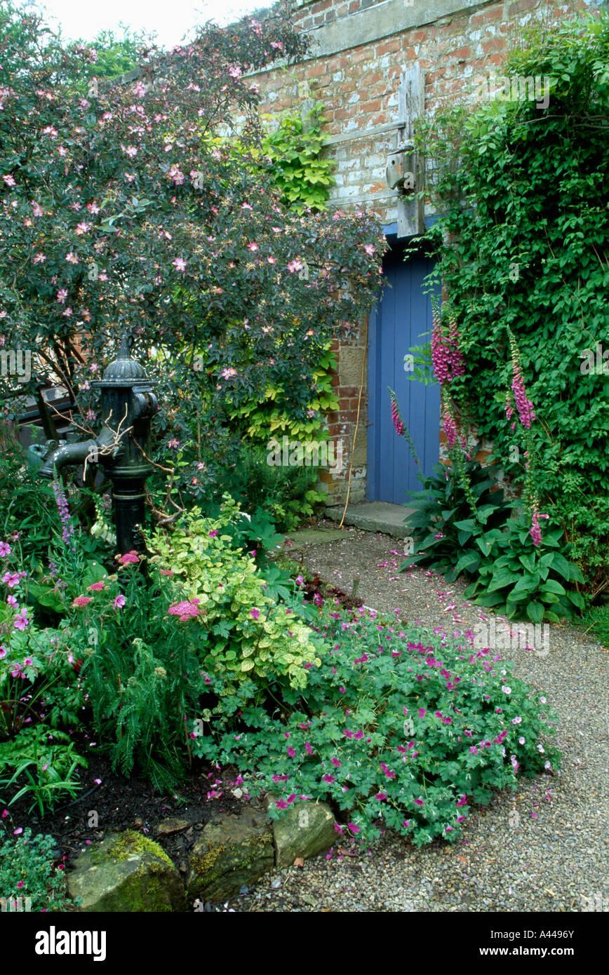 Blaue Tür Im Ummauerten Garten Mit Kiesweg Und Alte Wasserpumpe Im Rahmen