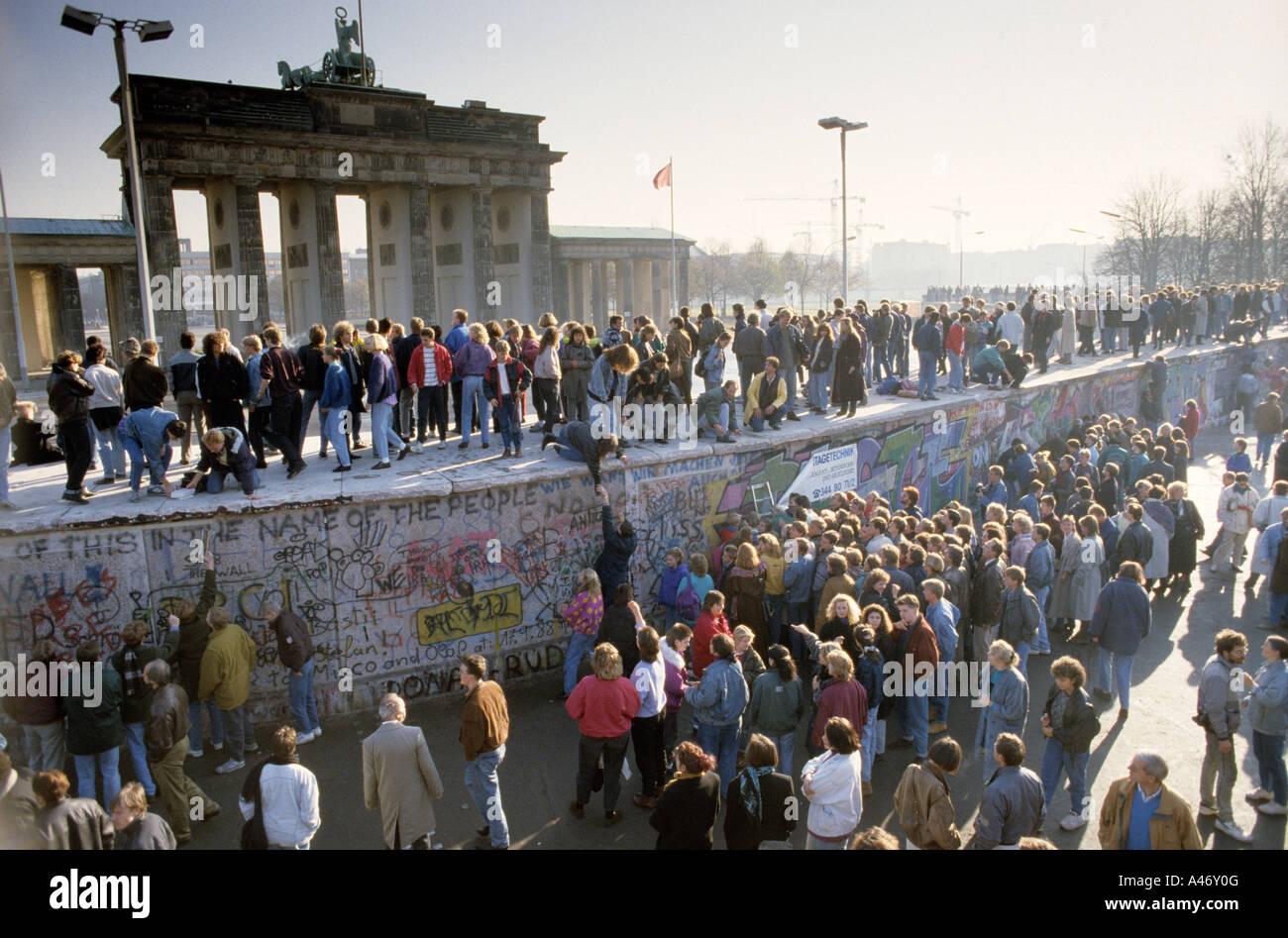 Fall der Berliner Mauer: Menschen aus Ost und West-Berliner Klettern an der Wand vor dem Brandenburger Tor, Berlin, Stockbild