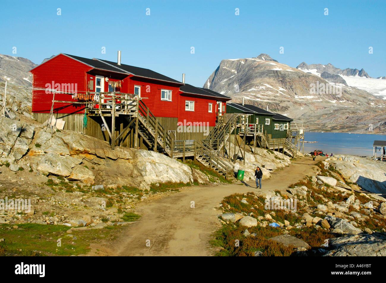 Bunte Häuser aus Holz gebaut auf Fels Fjord Berge und Gletscher im Hintergrund Tiniteqilaaq Eastgreenland Stockbild
