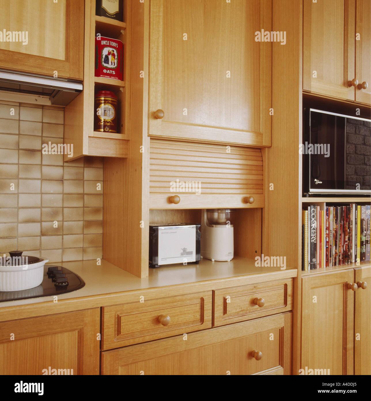 Nahaufnahme der Toaster im Küchenschrank mit Rollup-Holztür ...