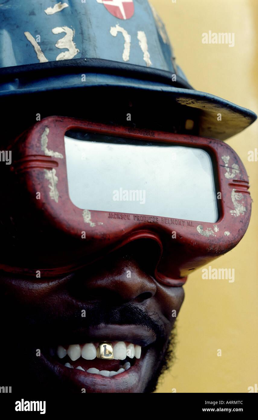 Eine grafische Nahaufnahme von einem schwarzen Bauarbeiter Gesicht zeigt einen Goldzahn Stockbild