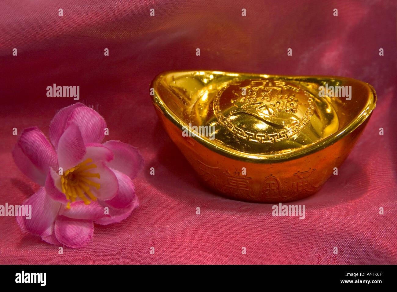 chinesische Goldbarren und Kunststoff Pflaumenblüte auf rotem ...