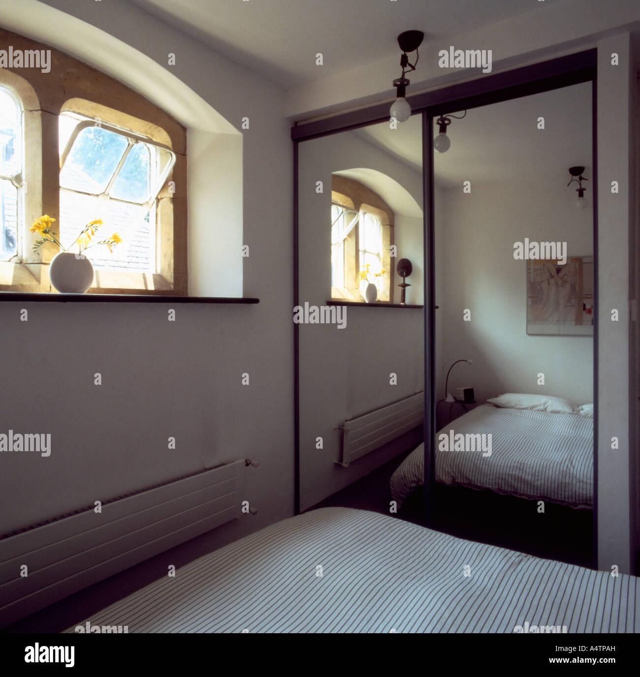 Großer Spiegel an Einbauschrank in kleinen weißen Schlafzimmer mit ...