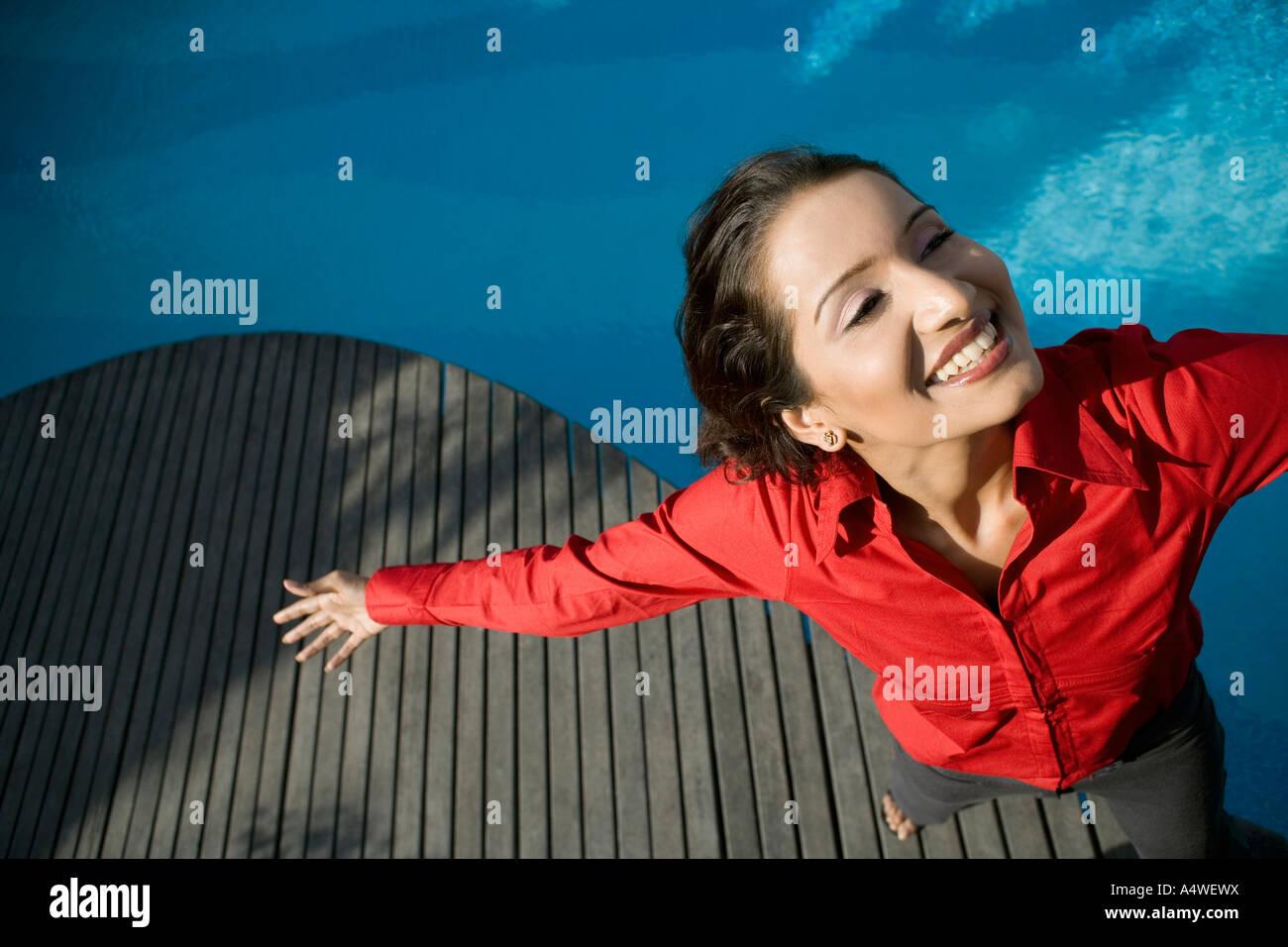 Geschäftsfrau, stehen am Swimmingpool mit ausgestreckten Armen Stockbild