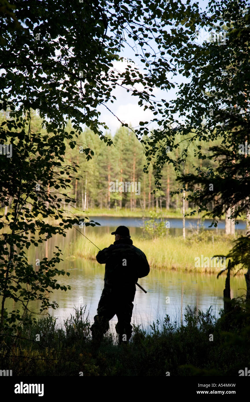 Silhouette von einem älteren Fischer angeln in einem kleinen Waldsee, Finnland Stockfoto