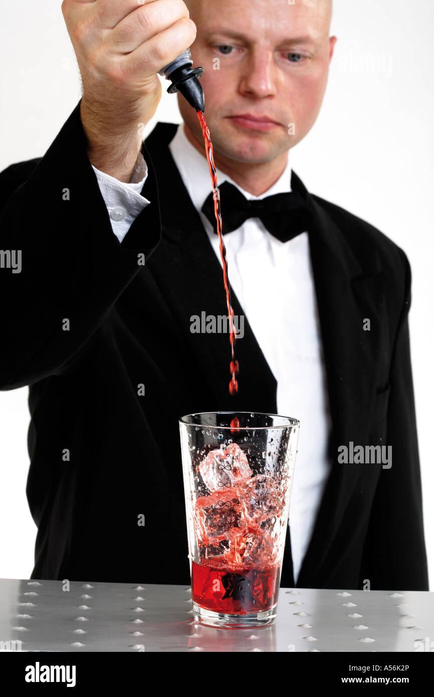Barkeeper strömenden Flüssigkeit in Glas Stockbild