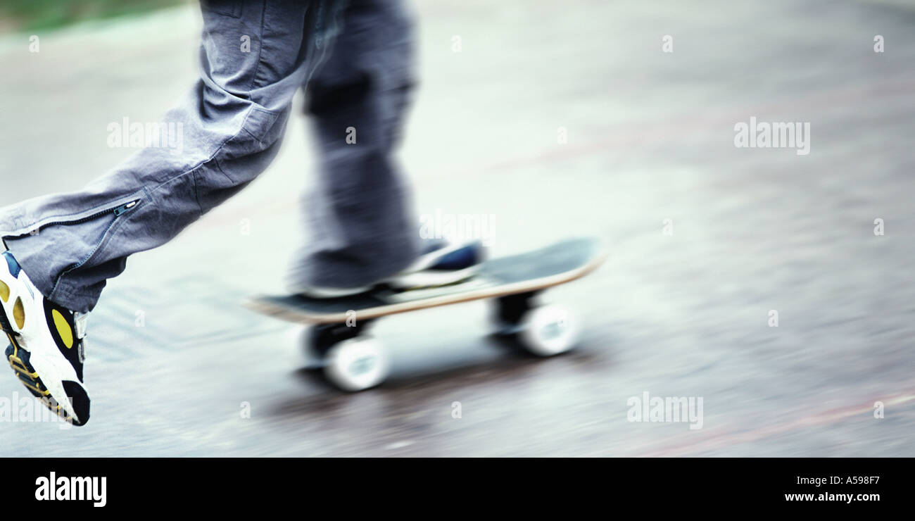 nahaufnahme eines jungen beine und fe auf skateboard bewegung stockbild - Skateboard Bank Beine