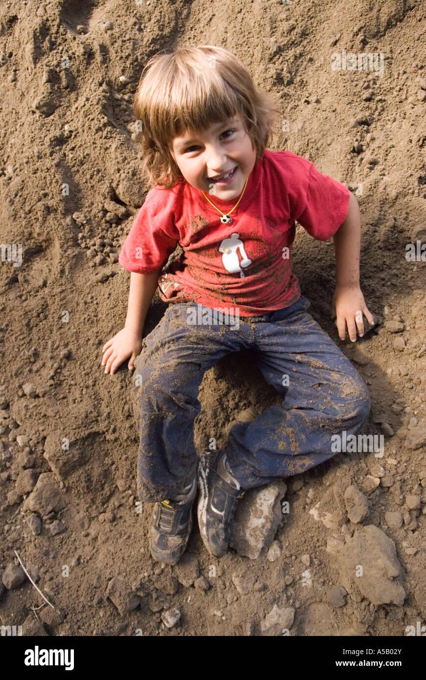 7 Jahre alten Sohn abspringen Sandhaufen im Hinterhof Stockfoto