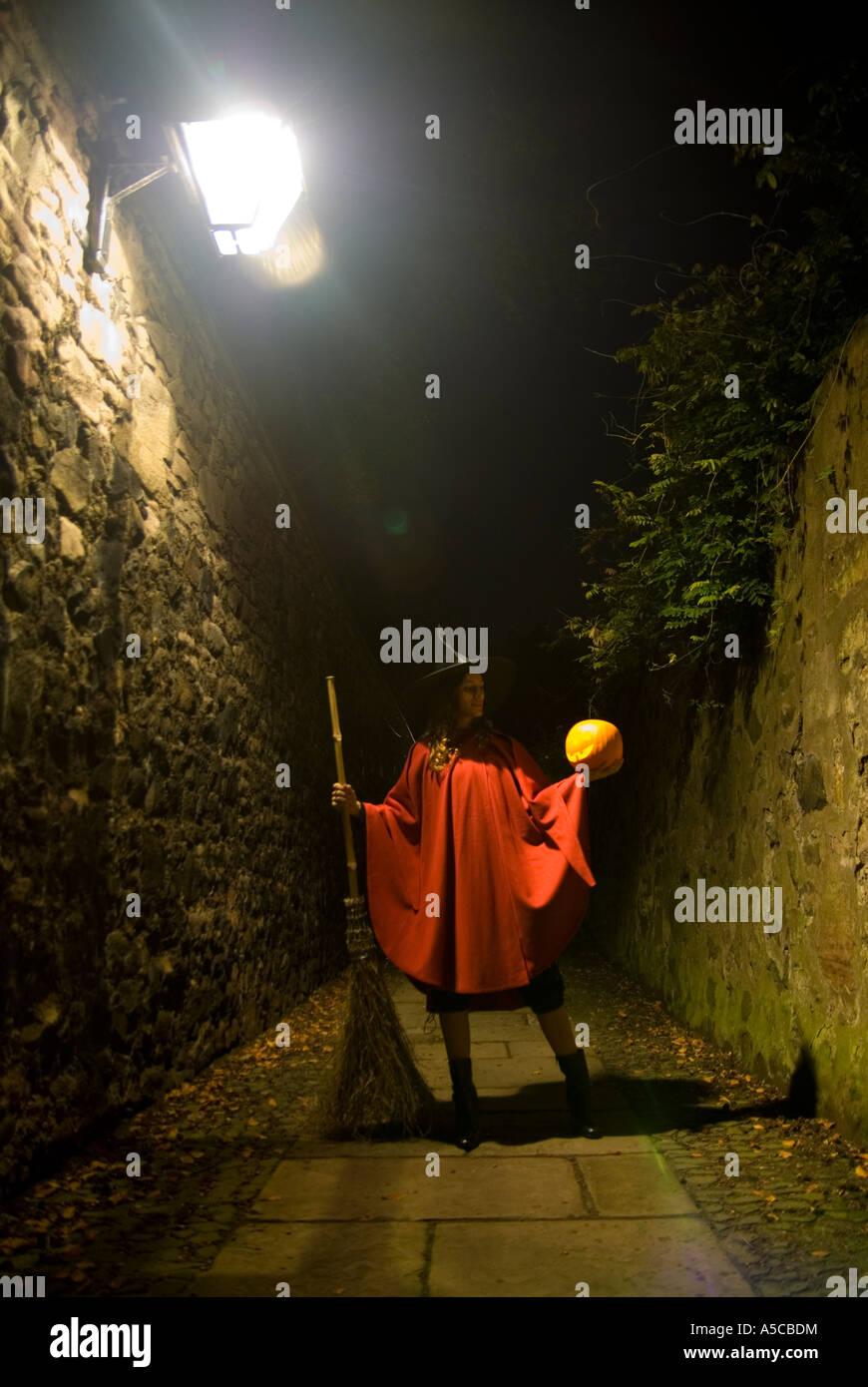 junge Frau, gekleidet wie eine Hexe hält ein pumking Stockbild