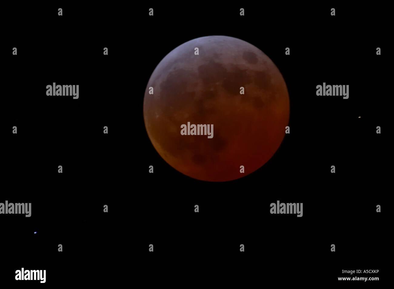 Der Mond leuchtet Ziegelrot während der totalität einer totale Mondfinsternis in Fortschritt als aus Nordirland Stockbild