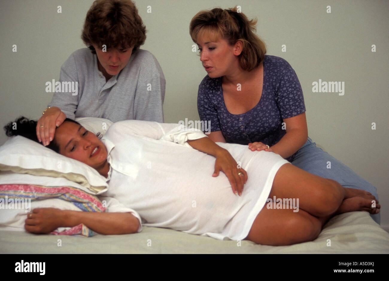 2 Frauen Hispanic Frau Während Der Geburt Zu Unterstützen Stockfoto