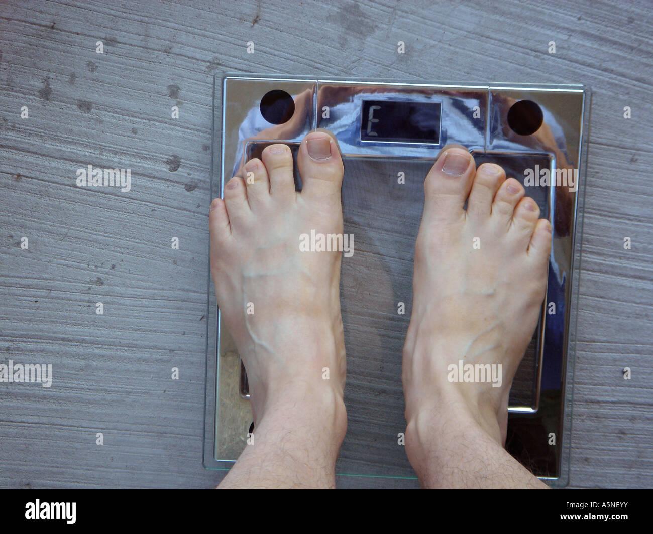 Fehler Gewicht A Mann s zwei nackten Füßen auf ein modernes elektronisches Glas und Chrom skalieren das Stockbild