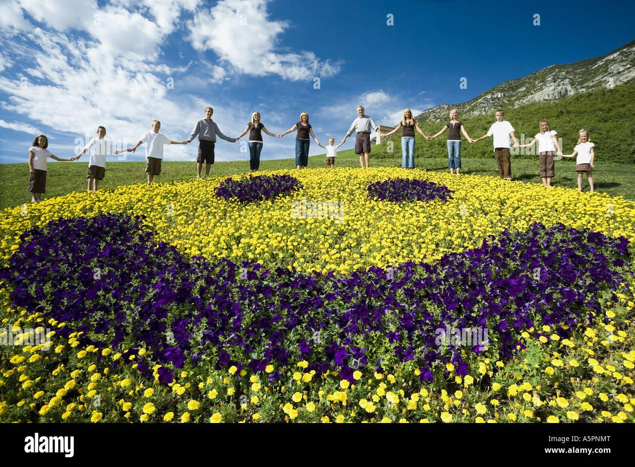 Großen Familiengruppe auf Hügel mit floralen glückliches Gesicht anzeigen Stockfoto
