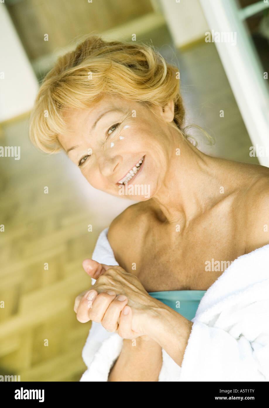 Ältere Frau Feuchtigkeitscreme auftragen Stockfoto