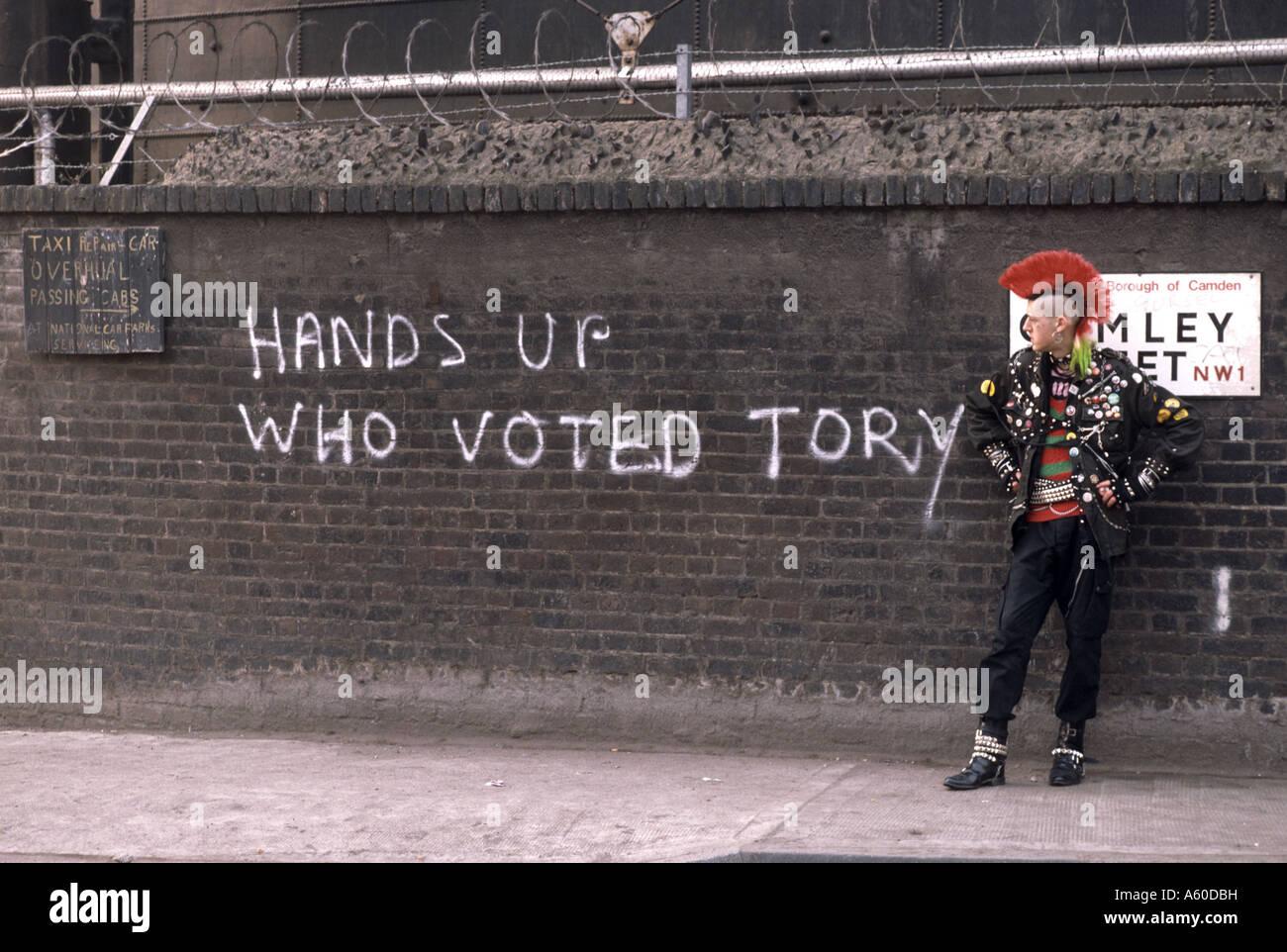 Punk-stand vor der Wand mit Graffiti sagen Hände hoch, wer ...
