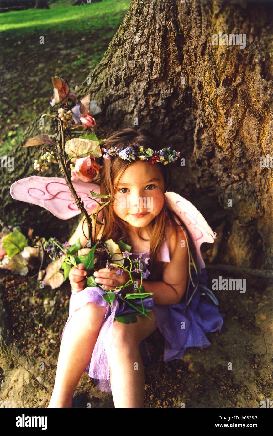 Fee Kind sitzt unter einem Baum schön wie der Zucker-Pflaume Fee Stockbild