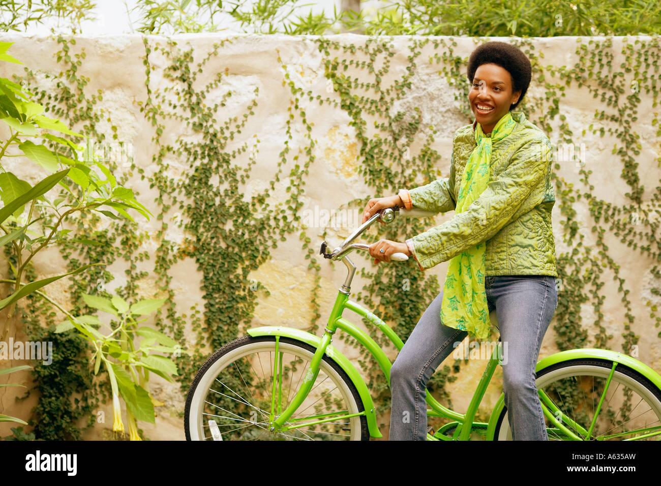 Junge Frau sitzt auf einem Fahrrad Stockbild