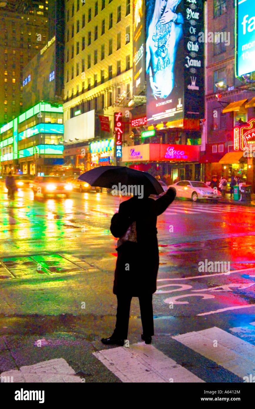 Mann hagelt Taxi mit Schirm im Regen in der Nacht, New York City Times Square, New York, USA Stockbild